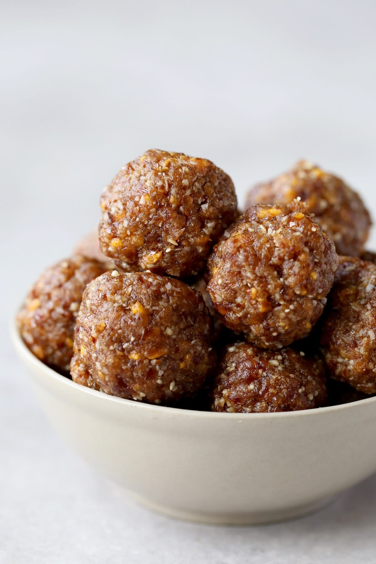 mango coconut energy bites piled high in a bowl