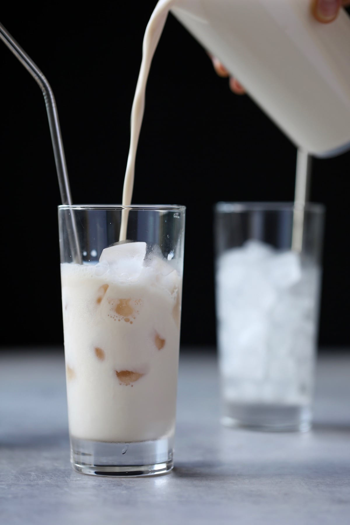 milk being poured into a glass of ice