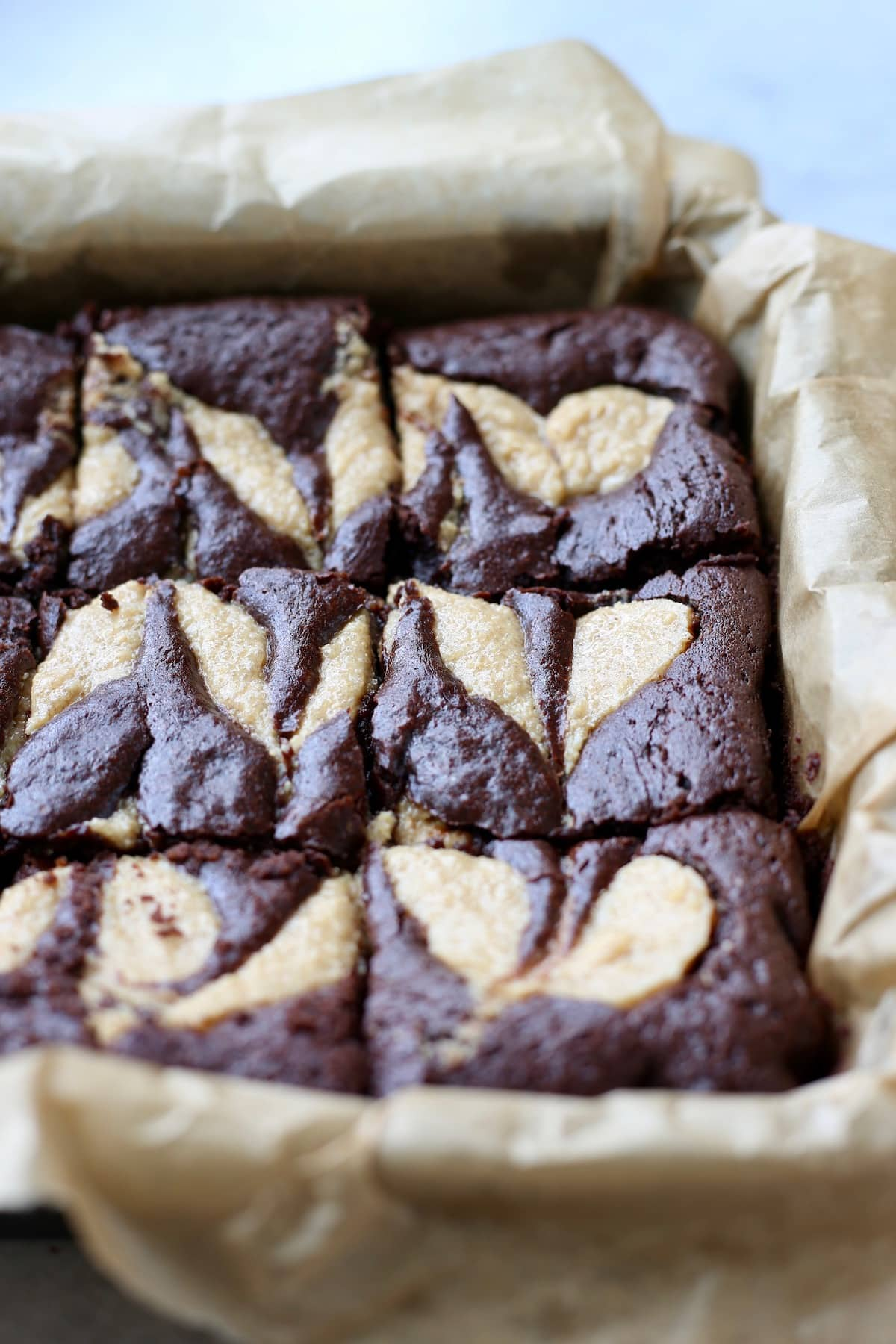 peanut butter brownies in a parchment paper lined baking tray