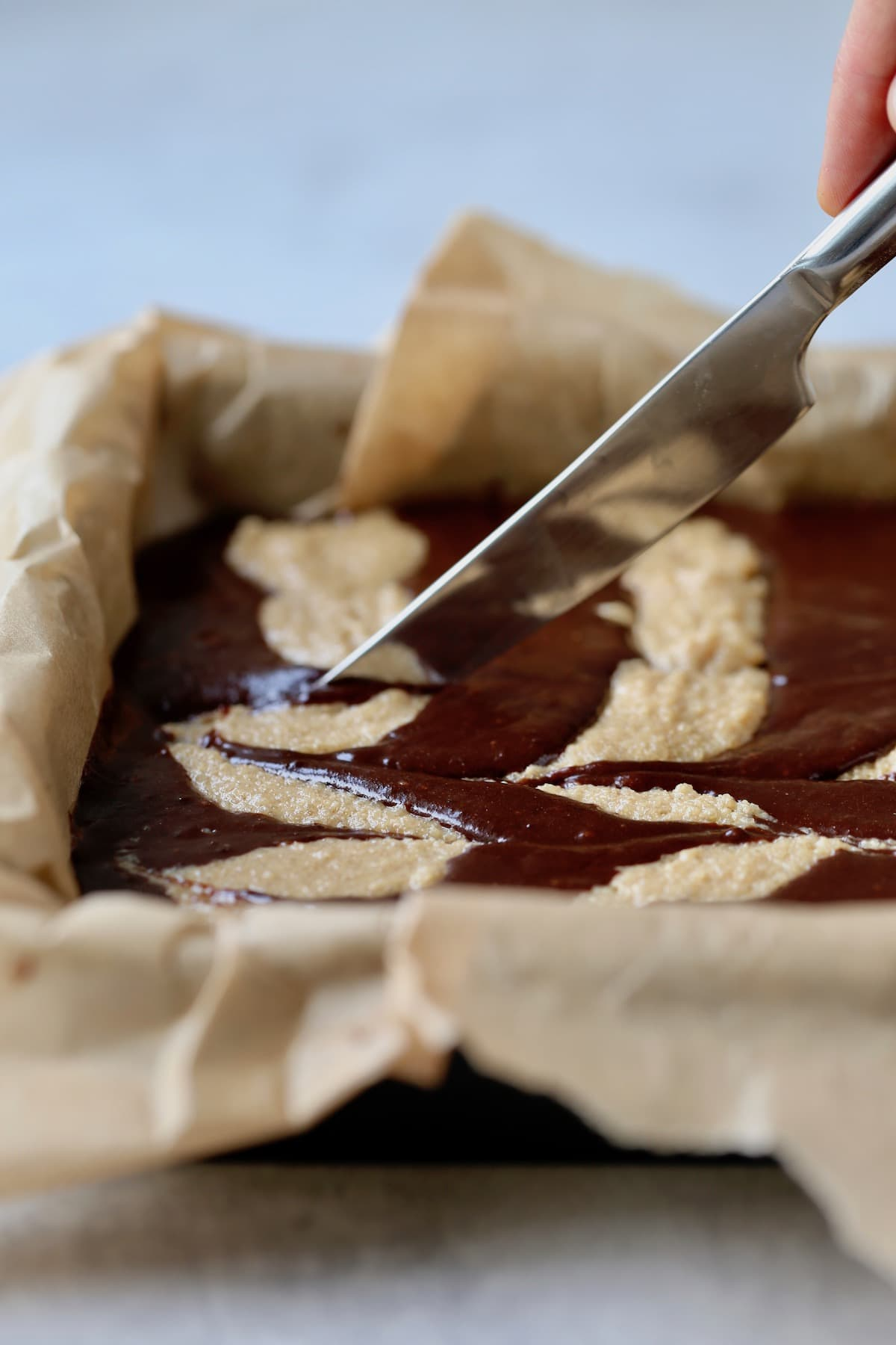 dragging a knife through peanut butter brownie batter to create a swirl