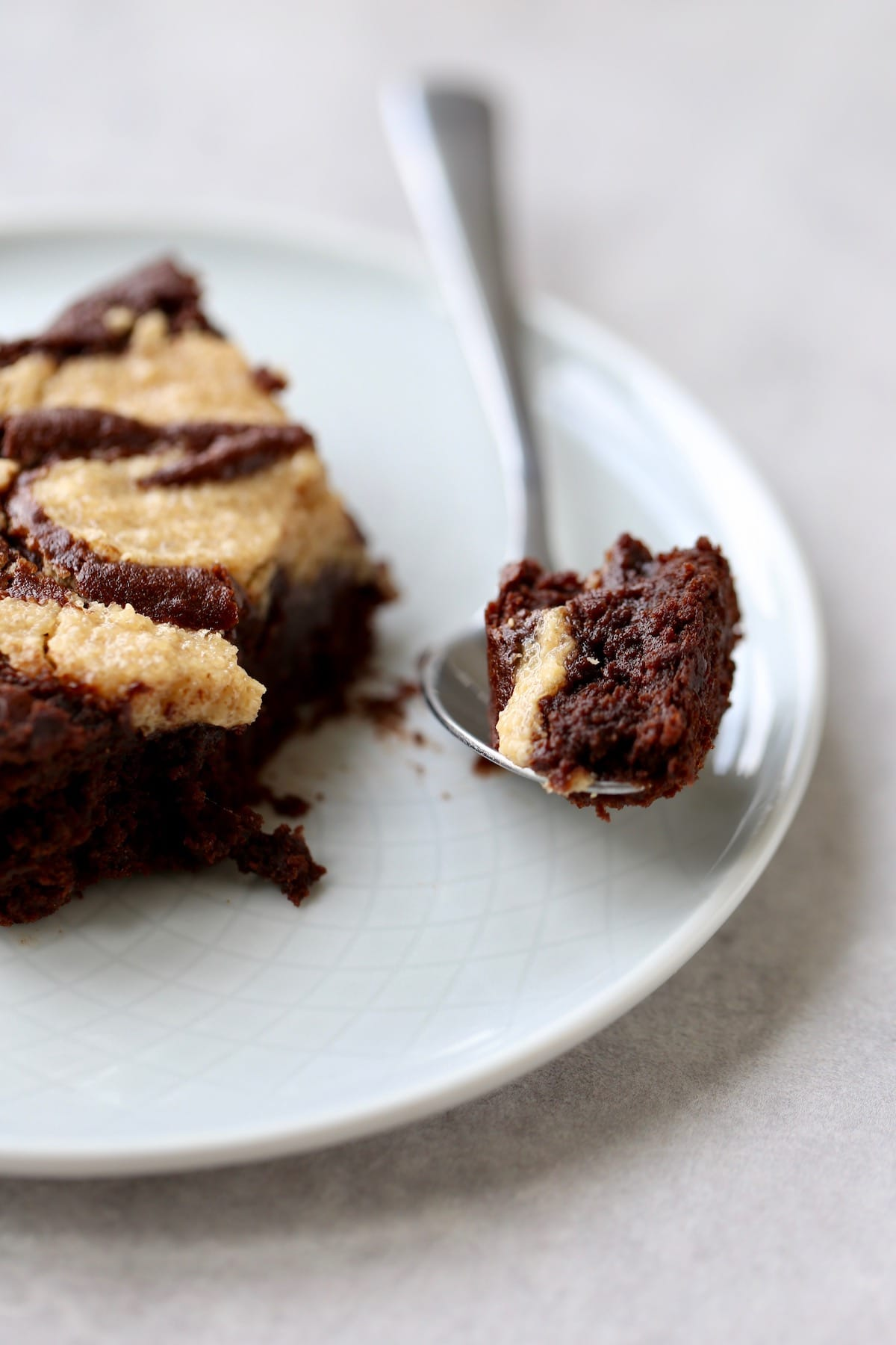 a fudgy bite of peanut butter swirl brownie on a spoon