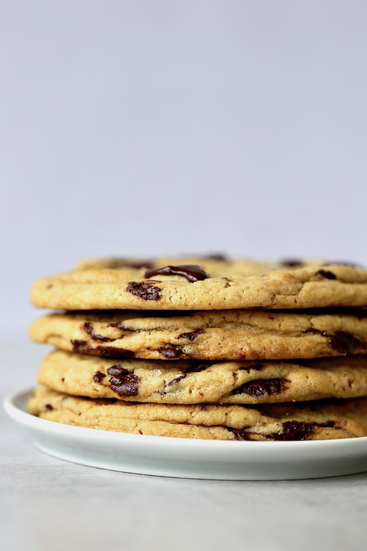 four jumbo chocolate chip cookies stacked on a plate