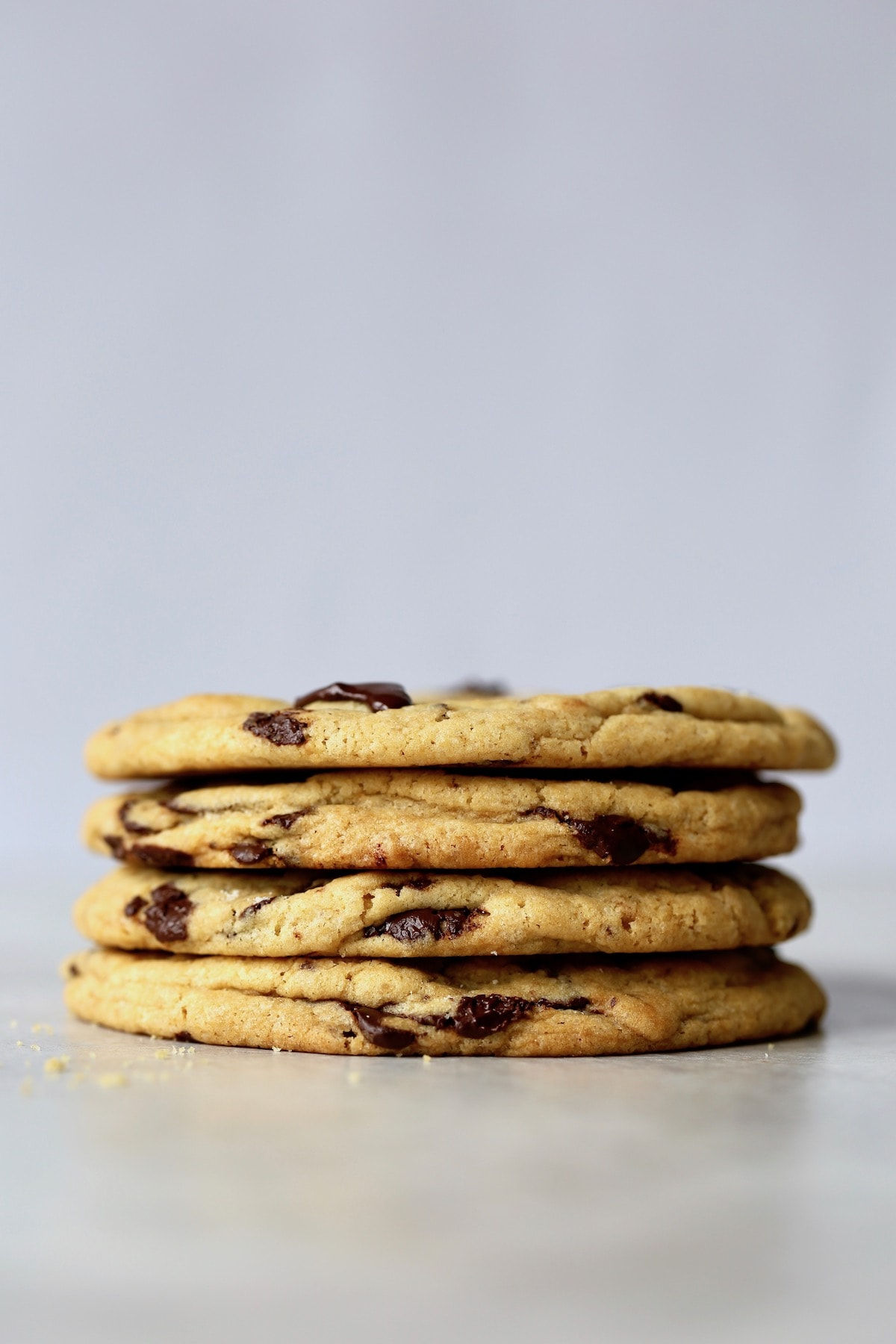 four bakery style chocolate chip cookies stacked on each other