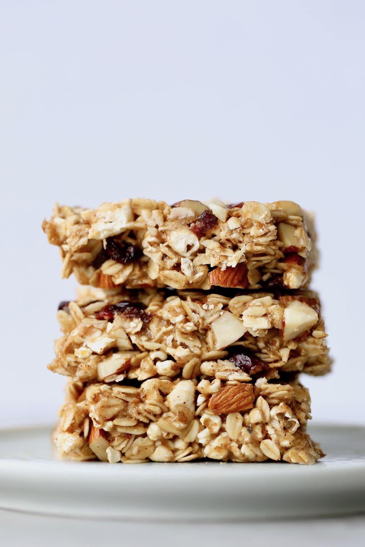 Three chewy, homemade popcorn granola bars stacked high on a plate