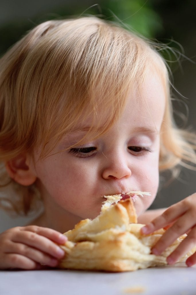 a little girl eating an apple turnover