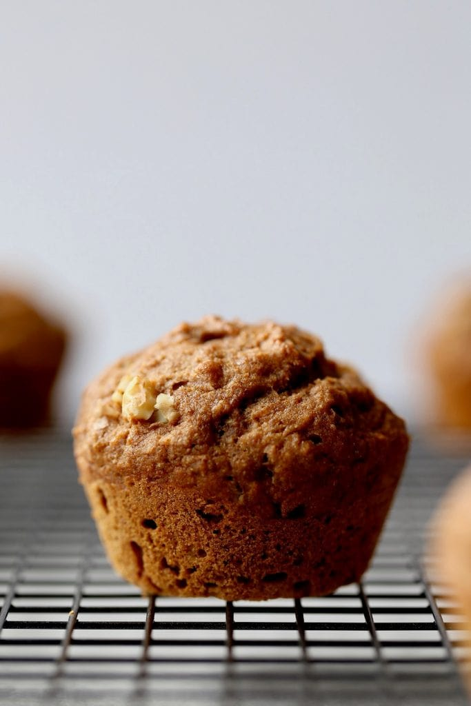 a vegan banana nut muffin cooling on a wire rack