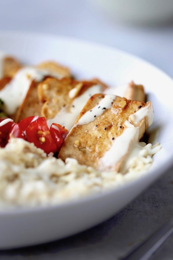 marinated, fried tofu on rice drizzled with tahini sauce