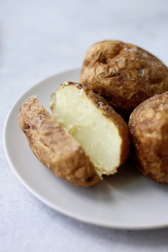 a baked potato cut vertically on a plate