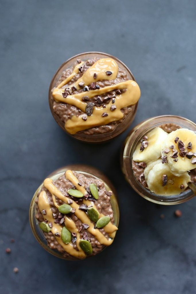 chia seed pudding cups topped with nut butter and cacao nibs