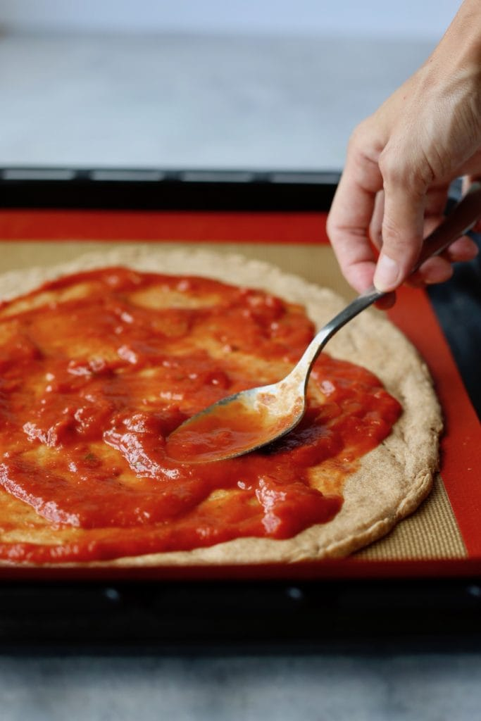 Marinara sauce being spread on whole wheat vegan no-yeast no-rise pizza dough with a spoon