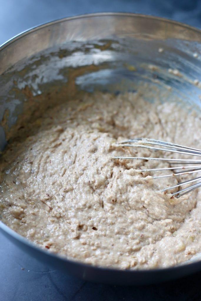 whole wheat vegan banana pancake batter being whisked in a bowl