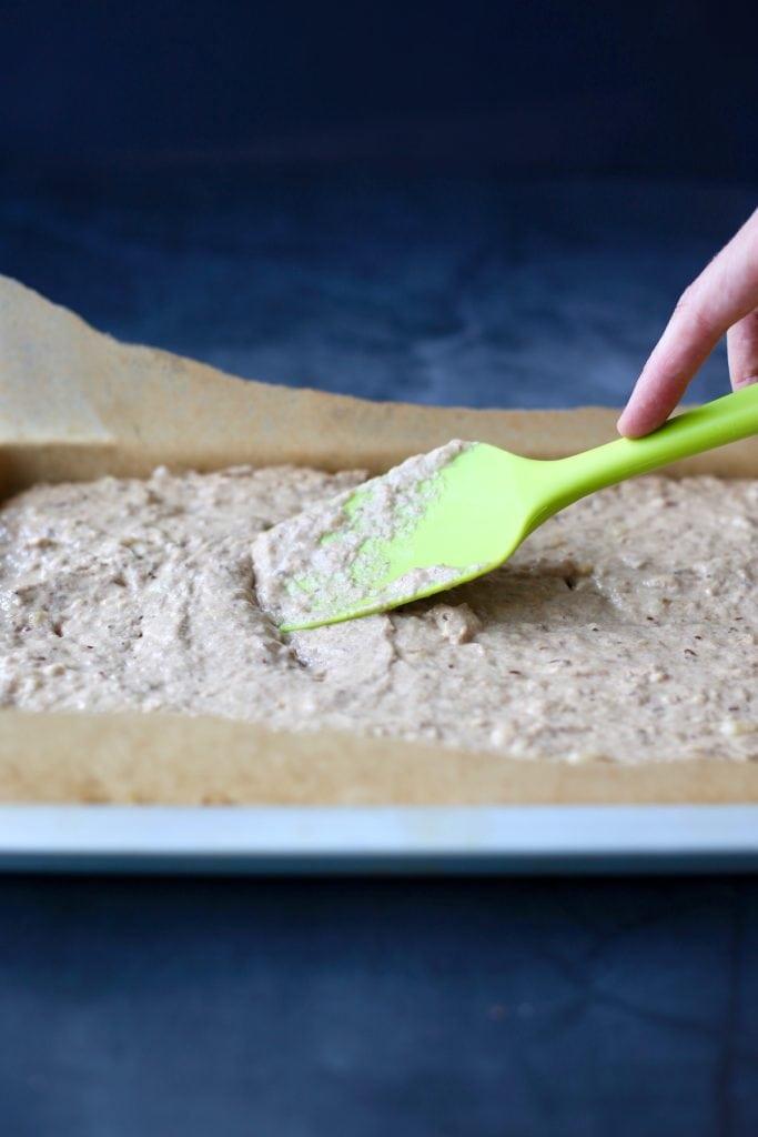 Whole wheat vegan banana pancake batter being spread in a sheet pan
