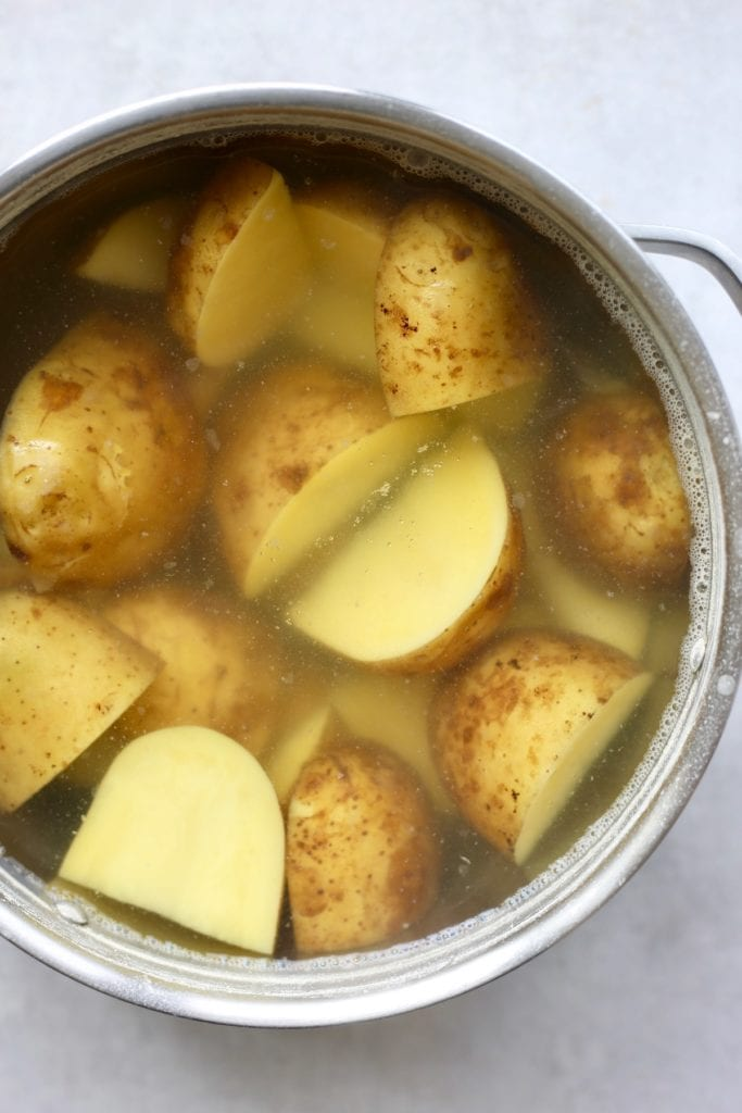 Quartered white potatoes boiling in a large pot