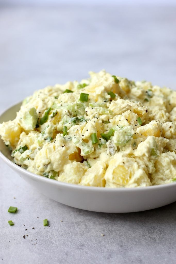Creamy vegan potato salad piled high in a bowl topped with green onion and black pepper