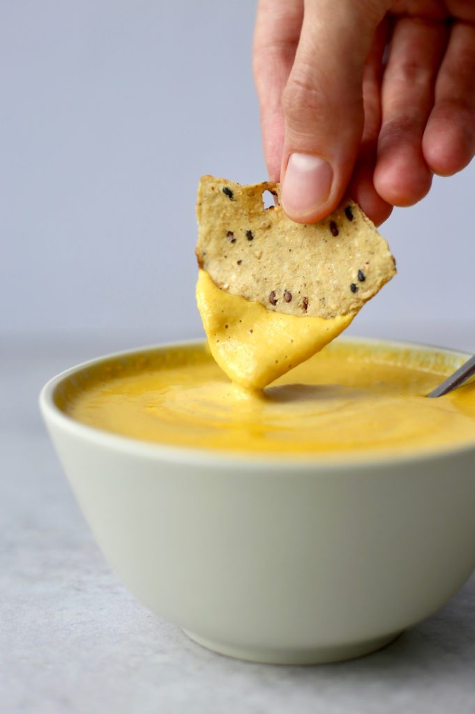 A multi-grain tortilla chip being dipped into vegan nacho cheese dip