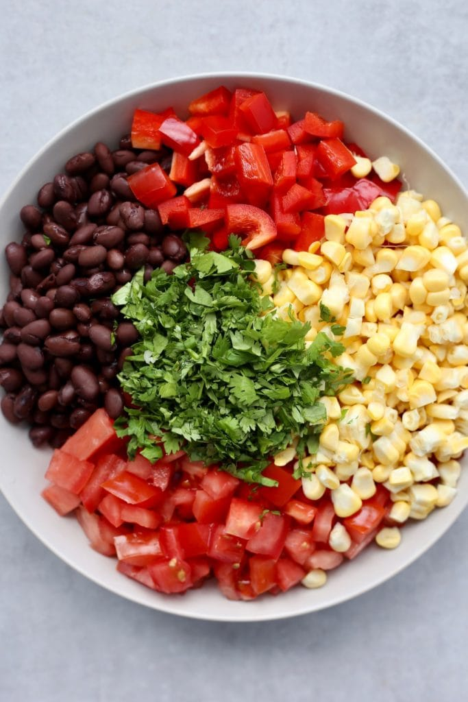 Al the ingredients for simple black bean and corn salad in a bowl