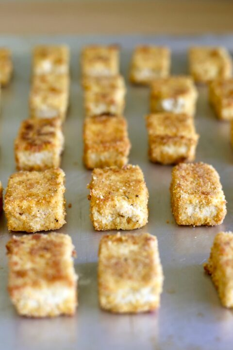almond flour baked tofu nuggets lined up on a baking sheet