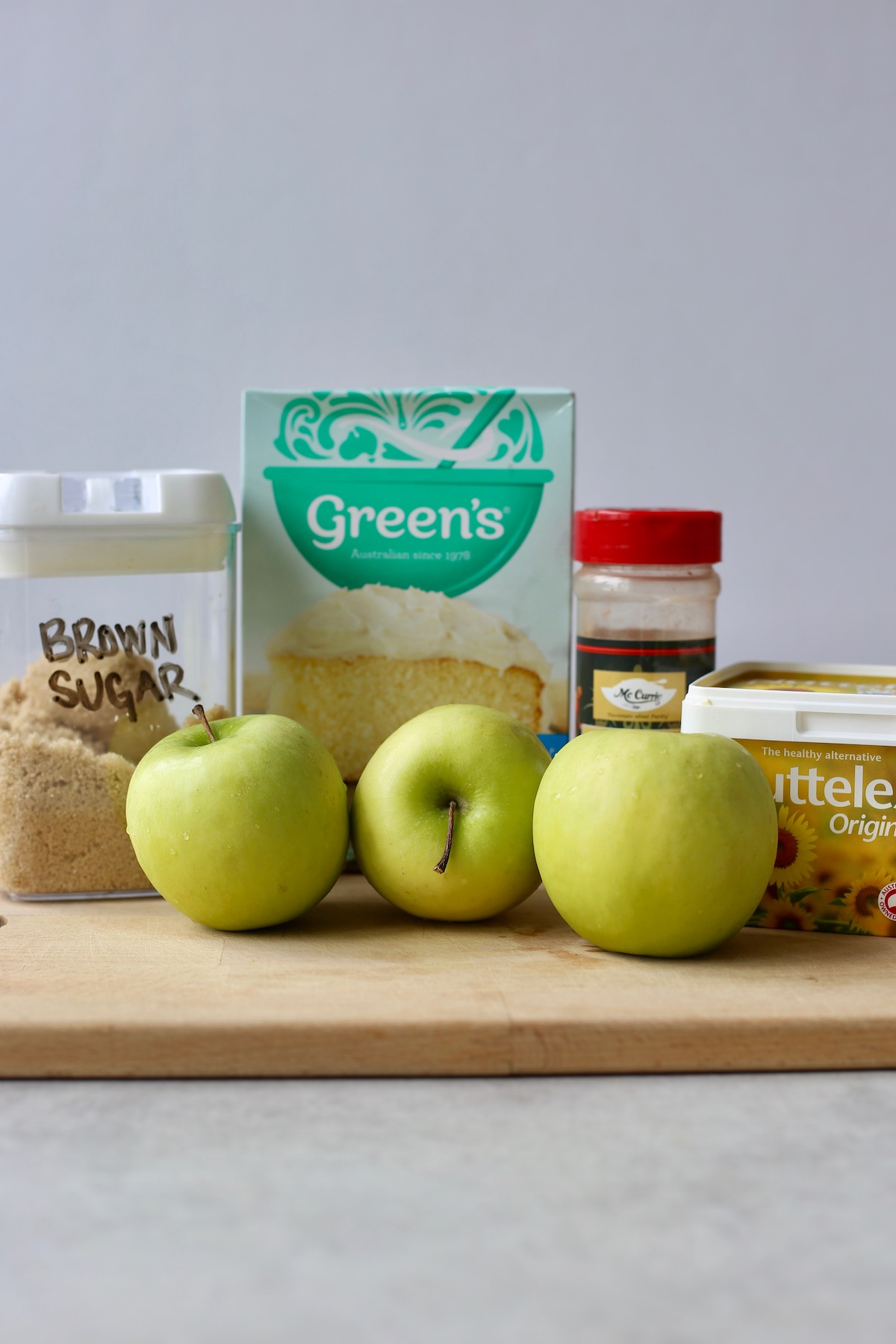 All the ingredients you'll need to make vegan apple dump cake laid out on a cutting board