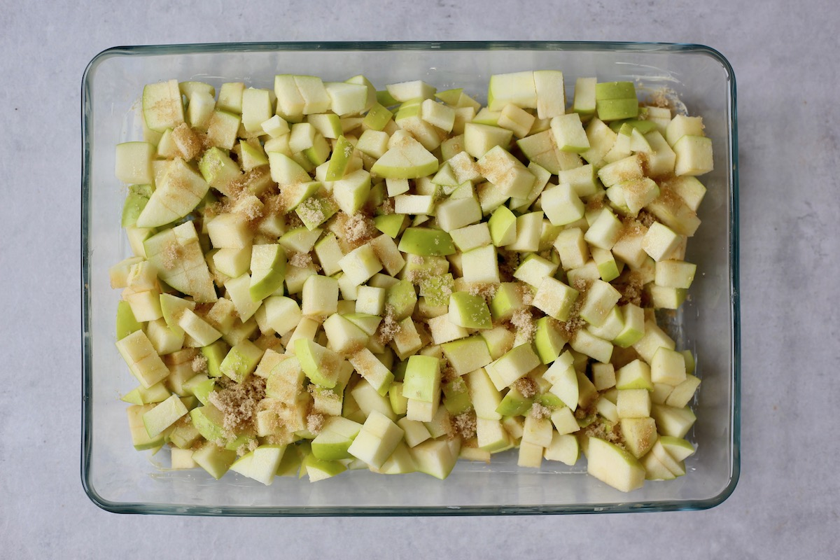 chopped green apples coated in brown sugar and cinnamon in a baking dish