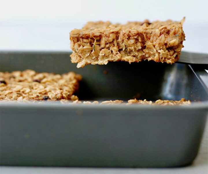 Baked oatmeal slice being pulled out the pan