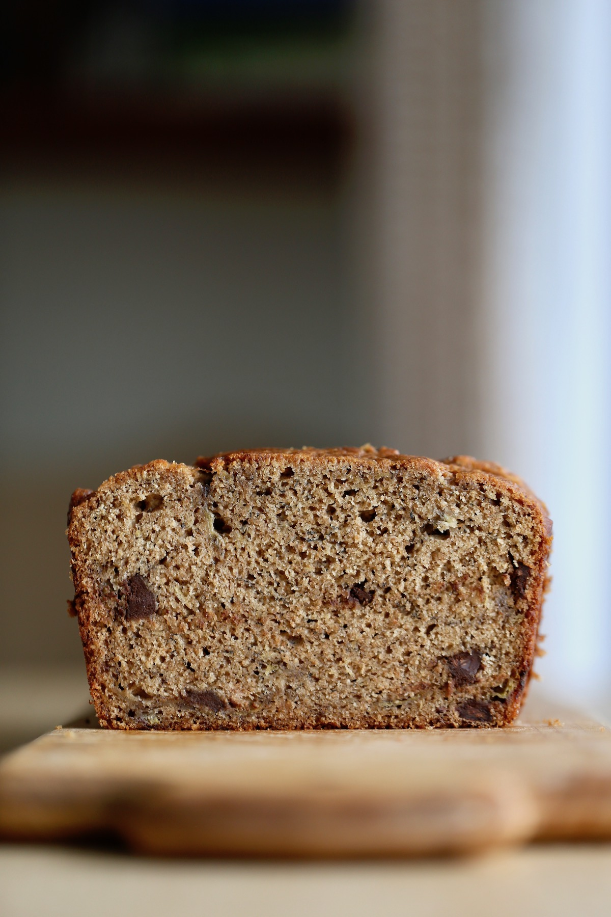 the cross section of a loaf of vegan chocolate chip banana bread on a cutting board