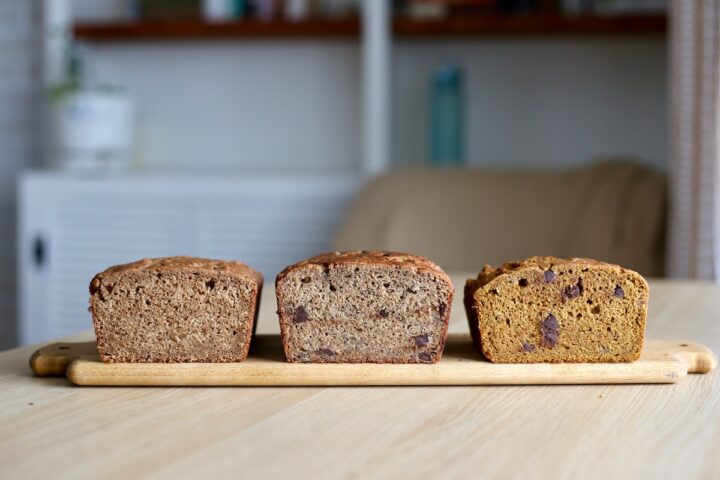 three different flavors of vegan quick bread lined up on a cutting board