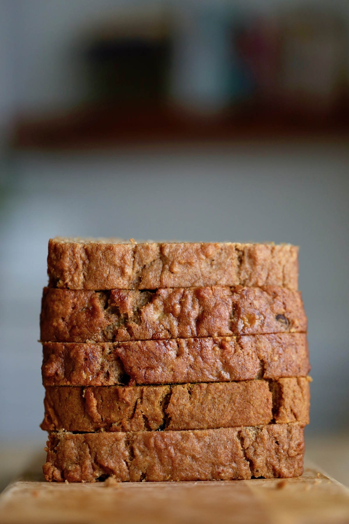 slices of three flavors of vegan quick bread stacked high on a cutting board