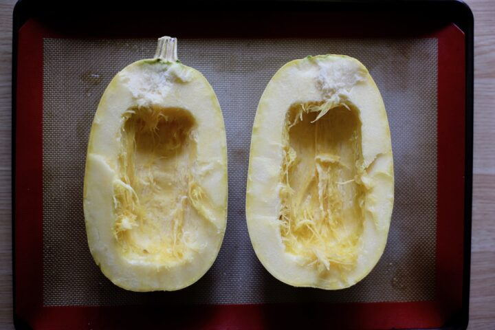a spaghetti squash cut in half lengthwise on a baking sheet before baking