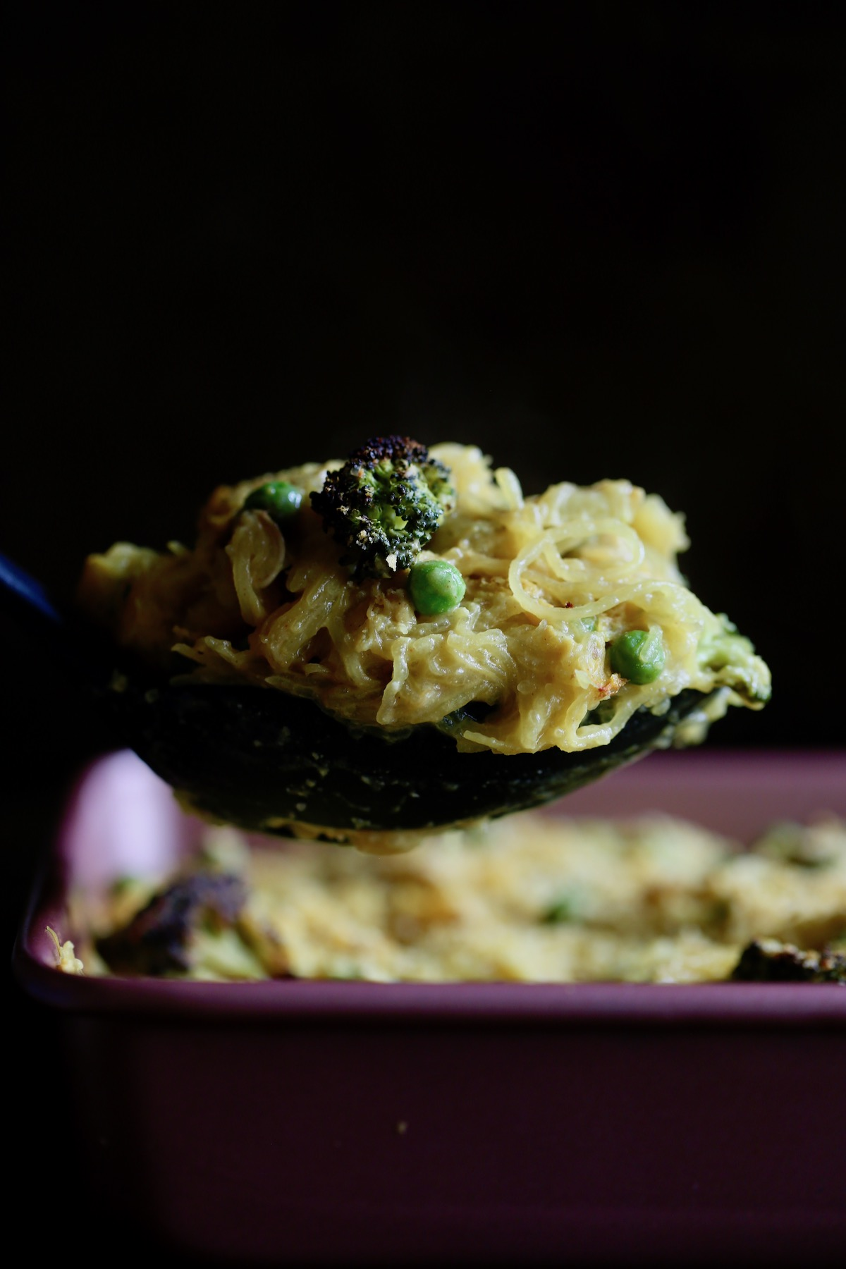a ladle scooping cheesy vegan spaghetti squash casserole out of a baking dish