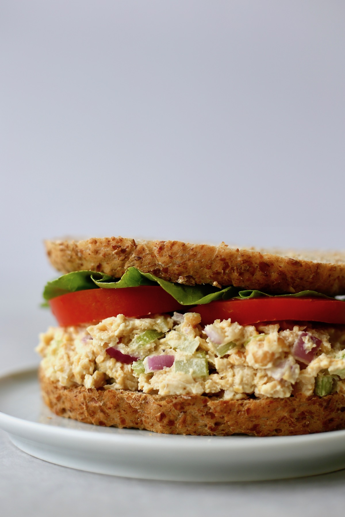 """Vegan Chickpea """"Tuna"""" Salad piled high on bread with lettuce and tomato"""