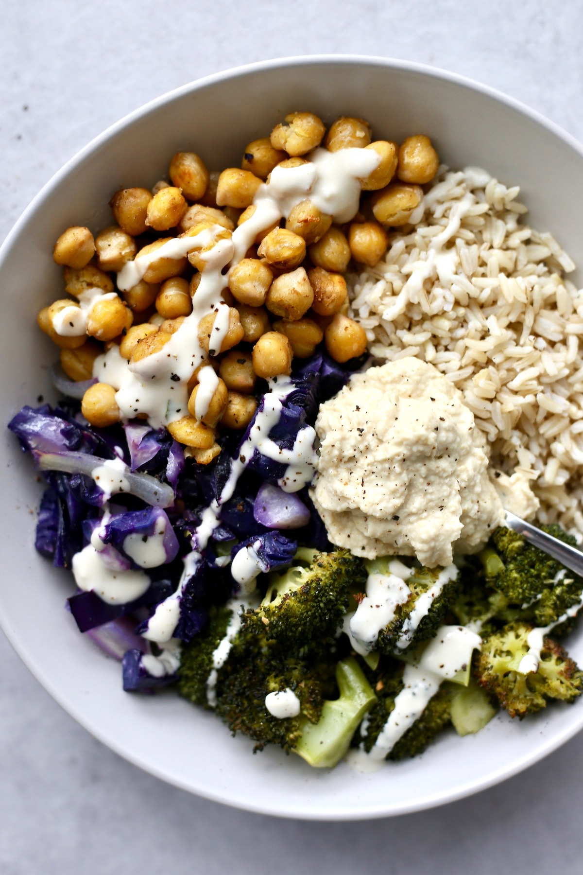 a bowl loaded with brown rice and roasted chickpeas, cabbage and broccoli, drizzled with tahini dressing