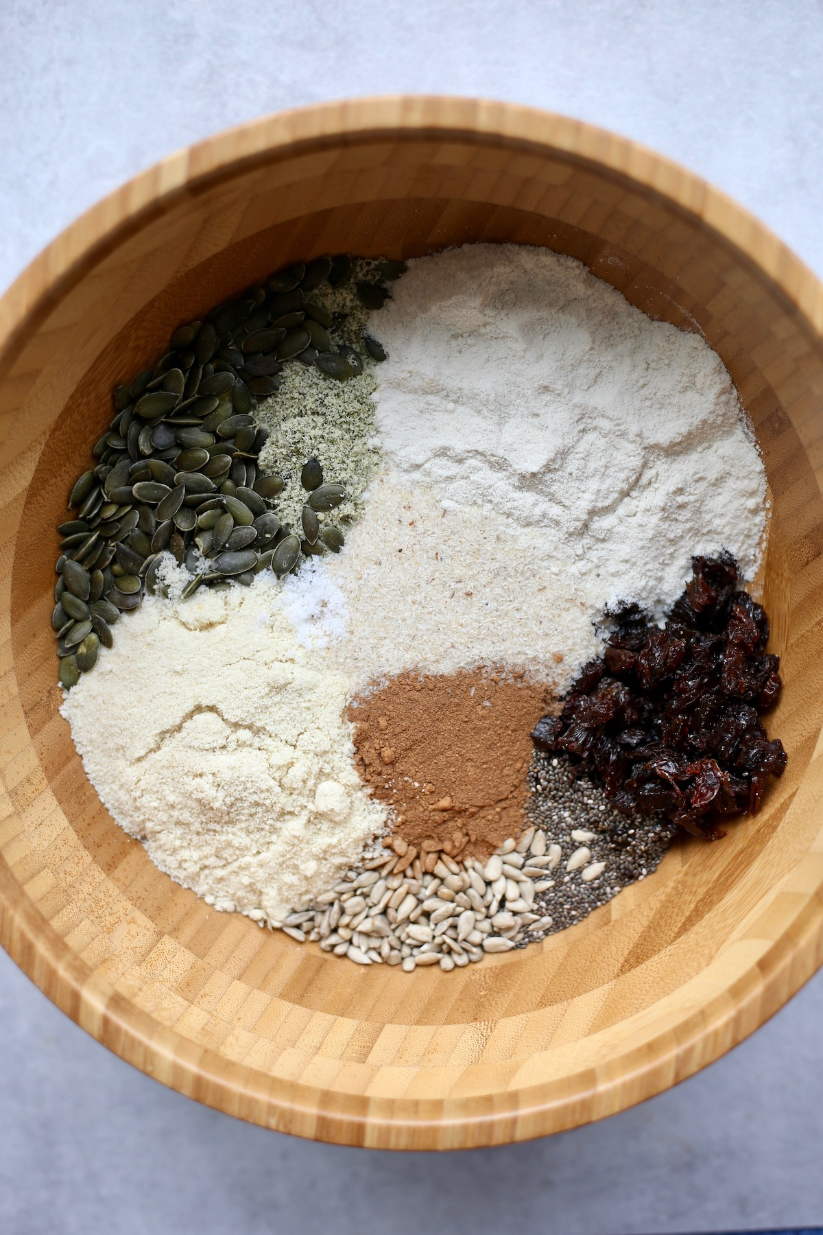 All the dry ingredients you'll need to make gluten-free cinnamon raisin seed bread in a large mixing bowl