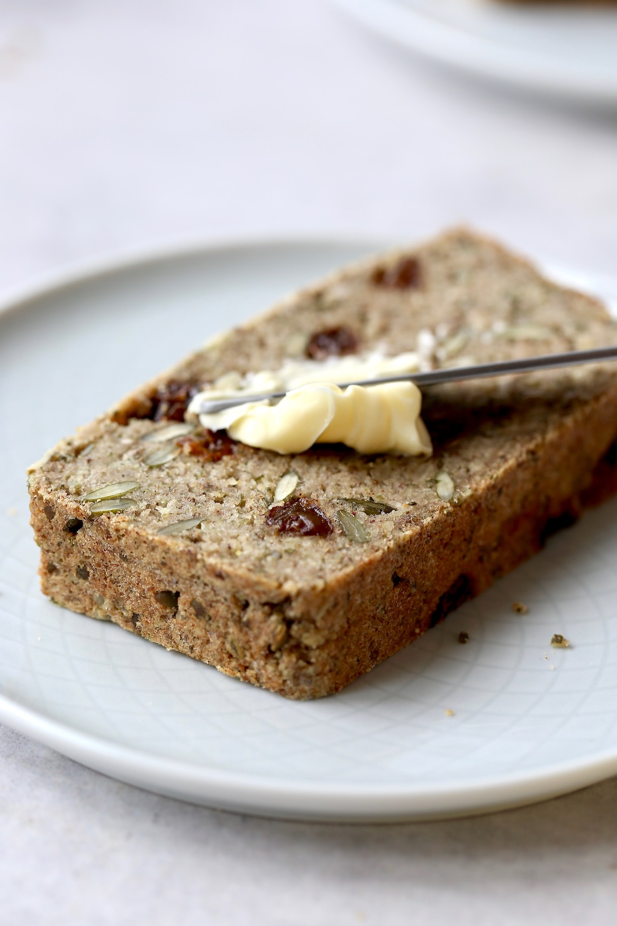 Cinnamon raisin seed bread being smeared with vegan butter