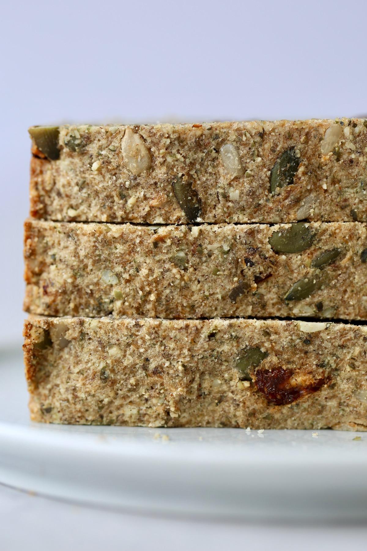 three slices of gluten free cinnamon raisin seed bread stacked on each other