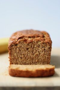 the BEST vegan banana bread being cut up on a cutting board