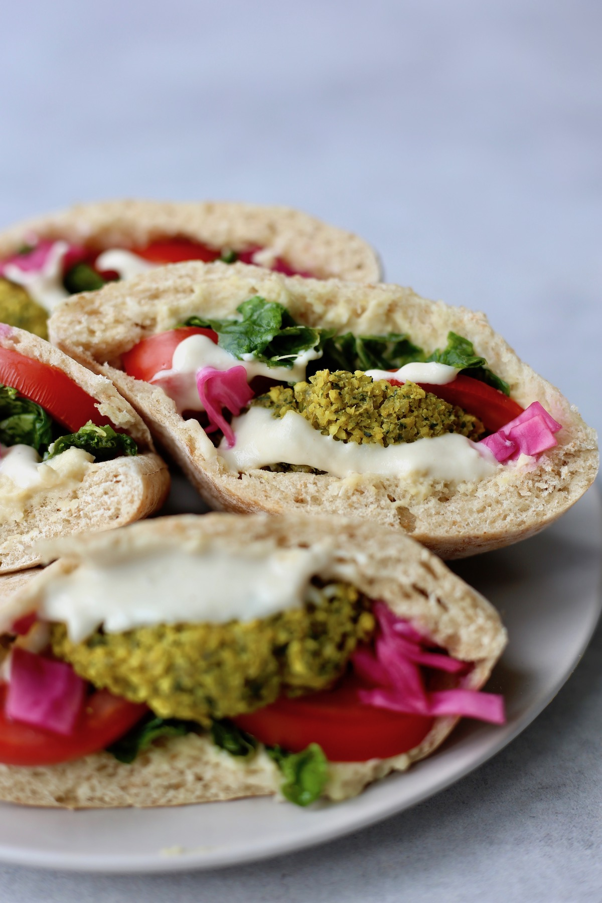 falafel pitas piled on a plate