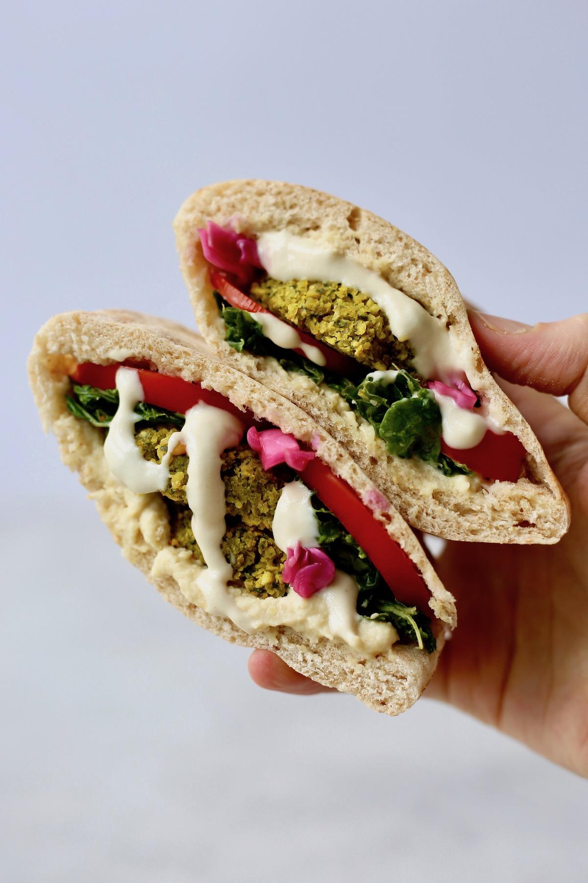 a hand holding a falafel pita wrap