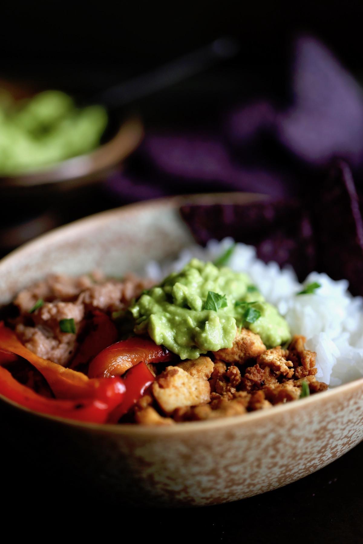 a vegan burrito bowl topped with homemade guacamole