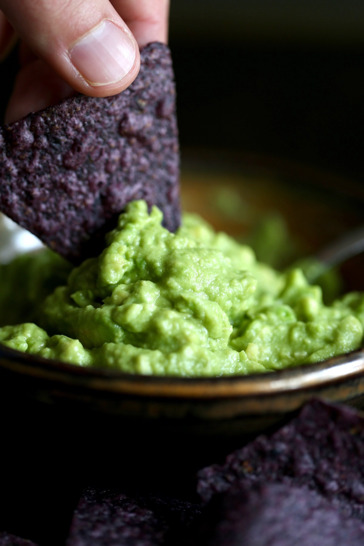 a blue corn tortilla chip scooping up some vibrant green guacamole