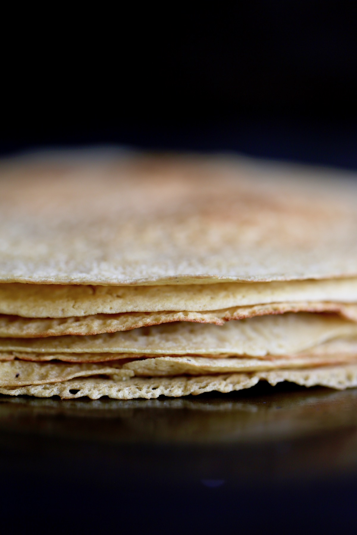 a stack of chickpea flour crepes on a pan