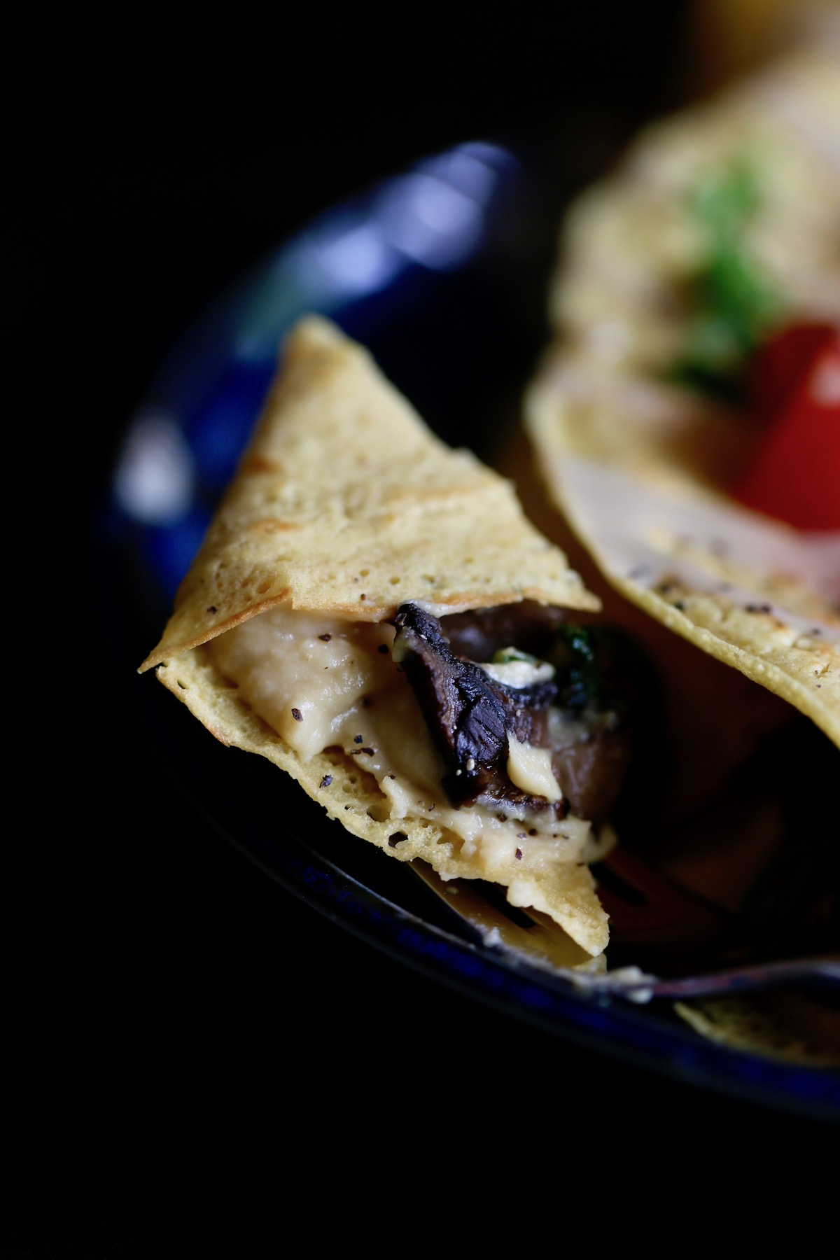 a bite of savory chickpea flour crepe filled with hummus and mushrooms