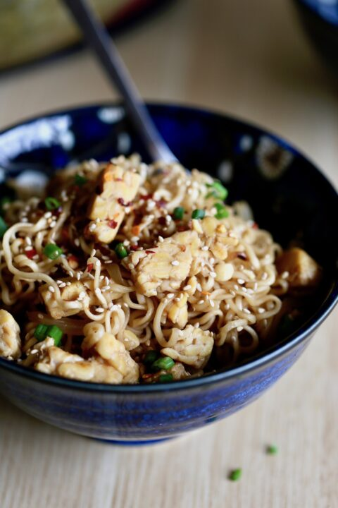 Quick Asian Ramen Noodles in a bowl with green onions, sesame seeds and red pepper flakes