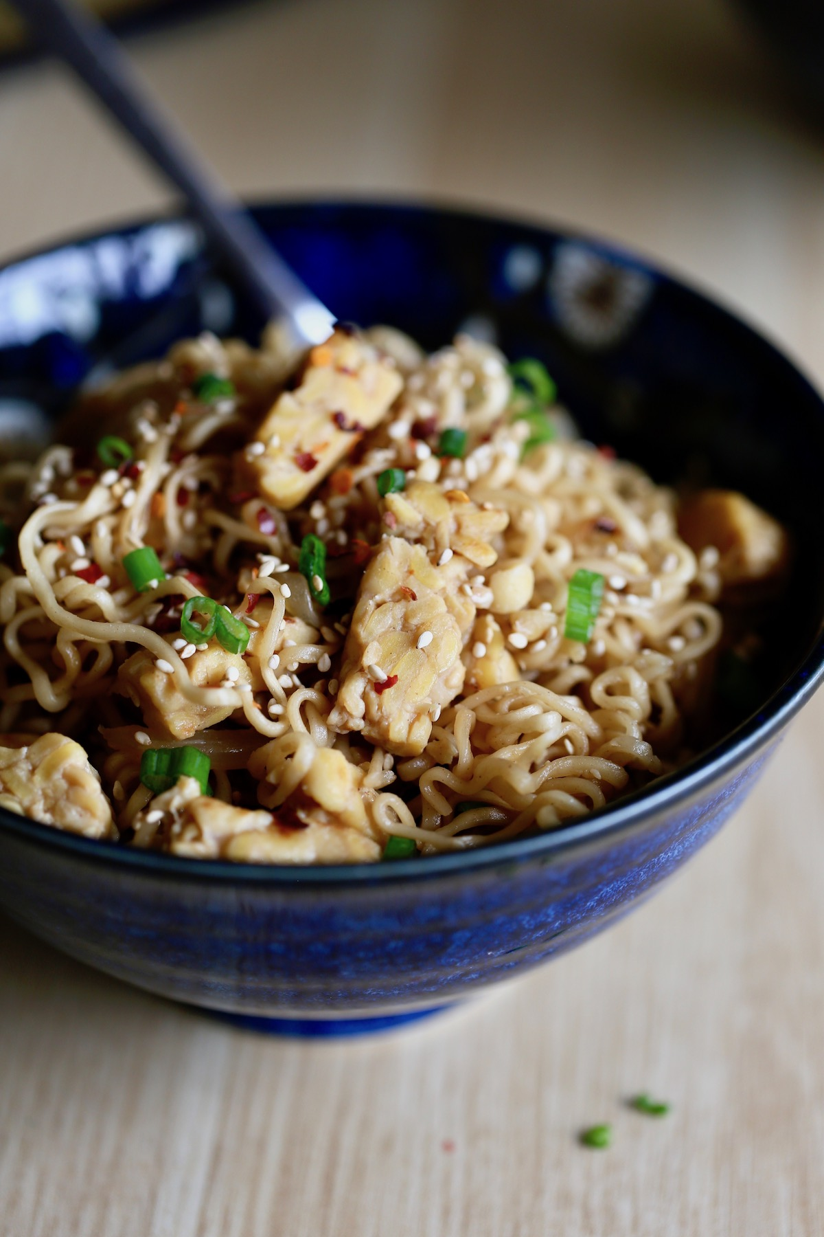 Quick Asian Ramen Noodles in a bowl topped with green onions and chili flakes