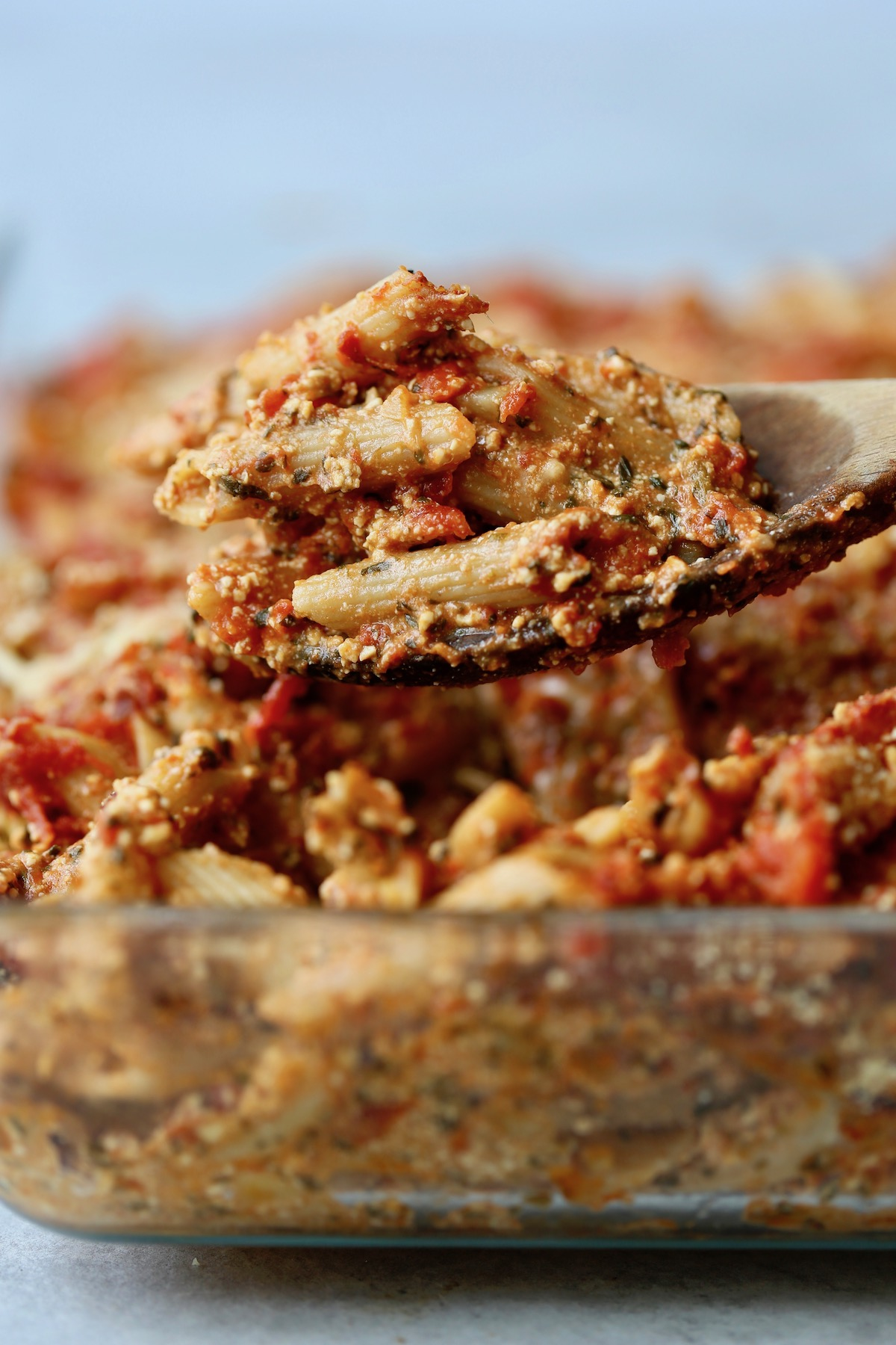 Easy vegan baked ziti with tofu ricotta piled high on a wooden spoon