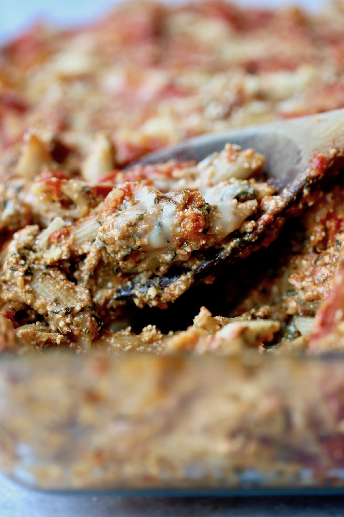 vegan and dairy-free baked ziti being scooped up with a wooden spoon