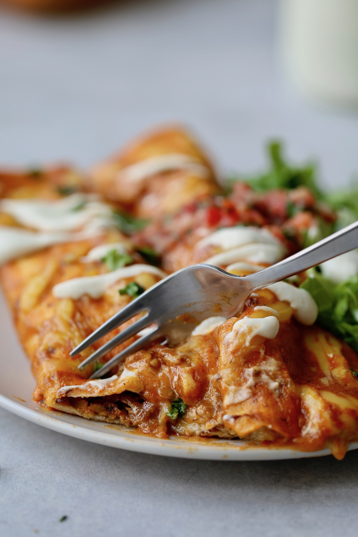 a fork cutting into cheesy vegan enchiladas
