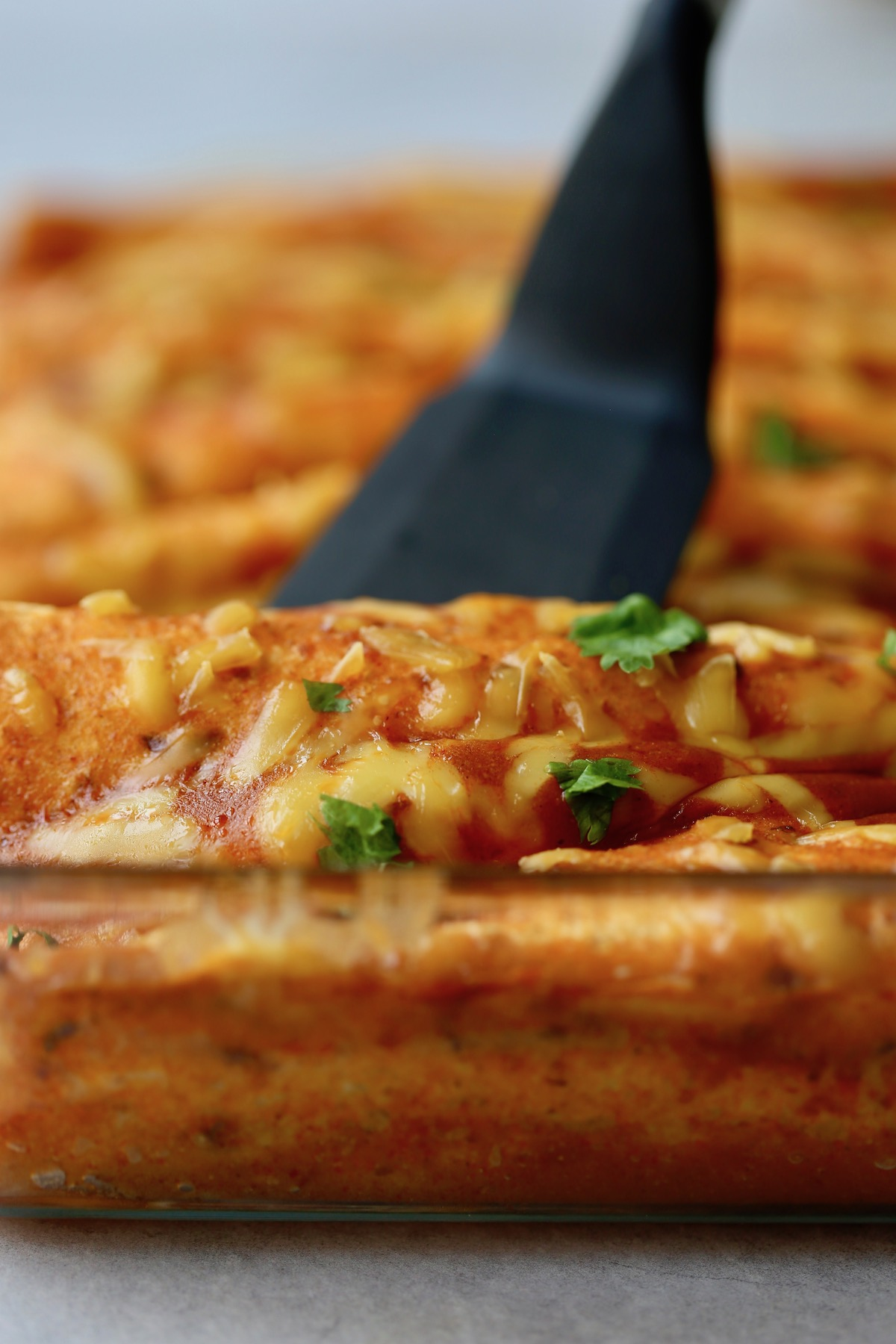 a spatula scooping up a serving of vegan enchiladas