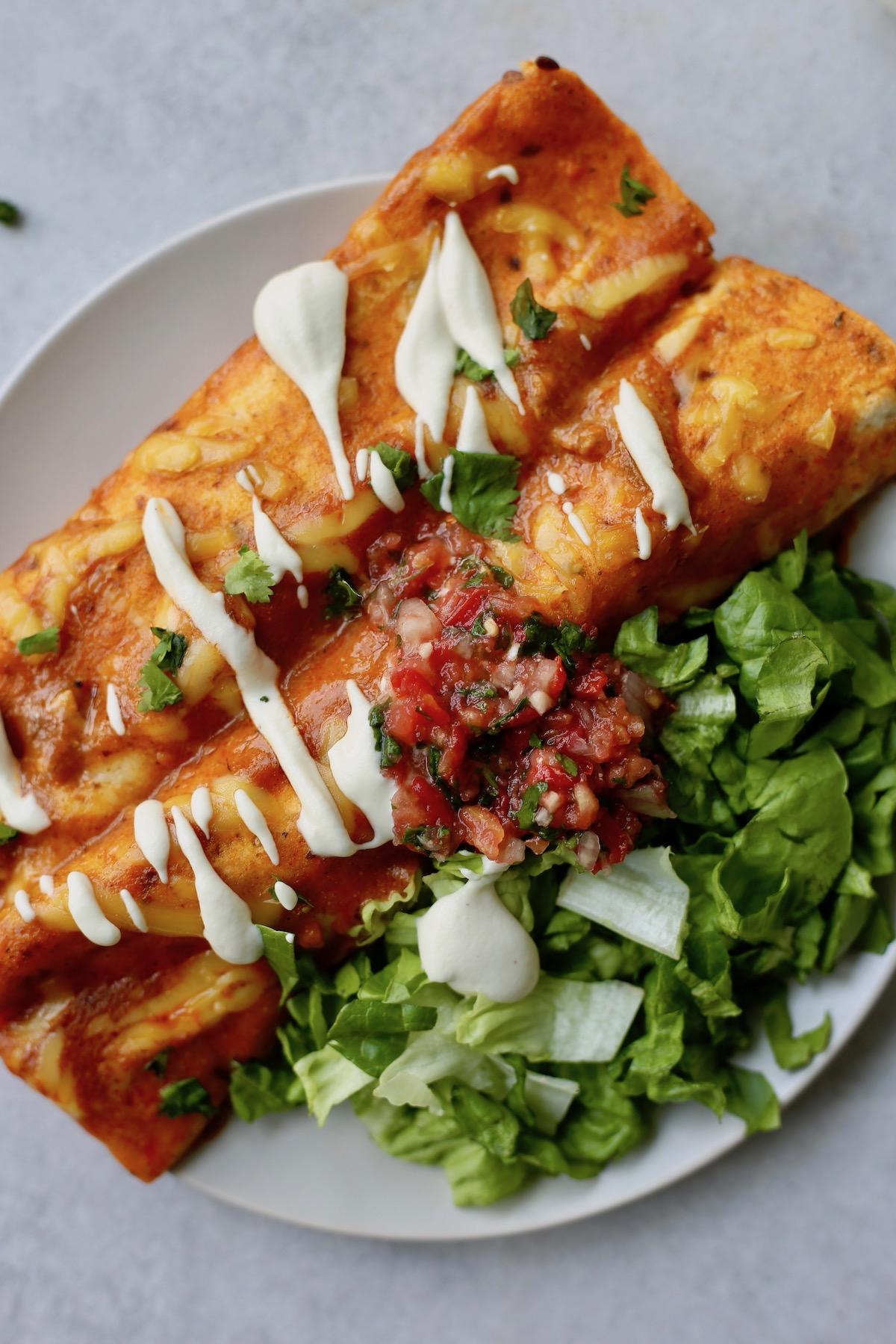 easy vegan enchiladas topped with cashew sour cream, salsa and cilantro