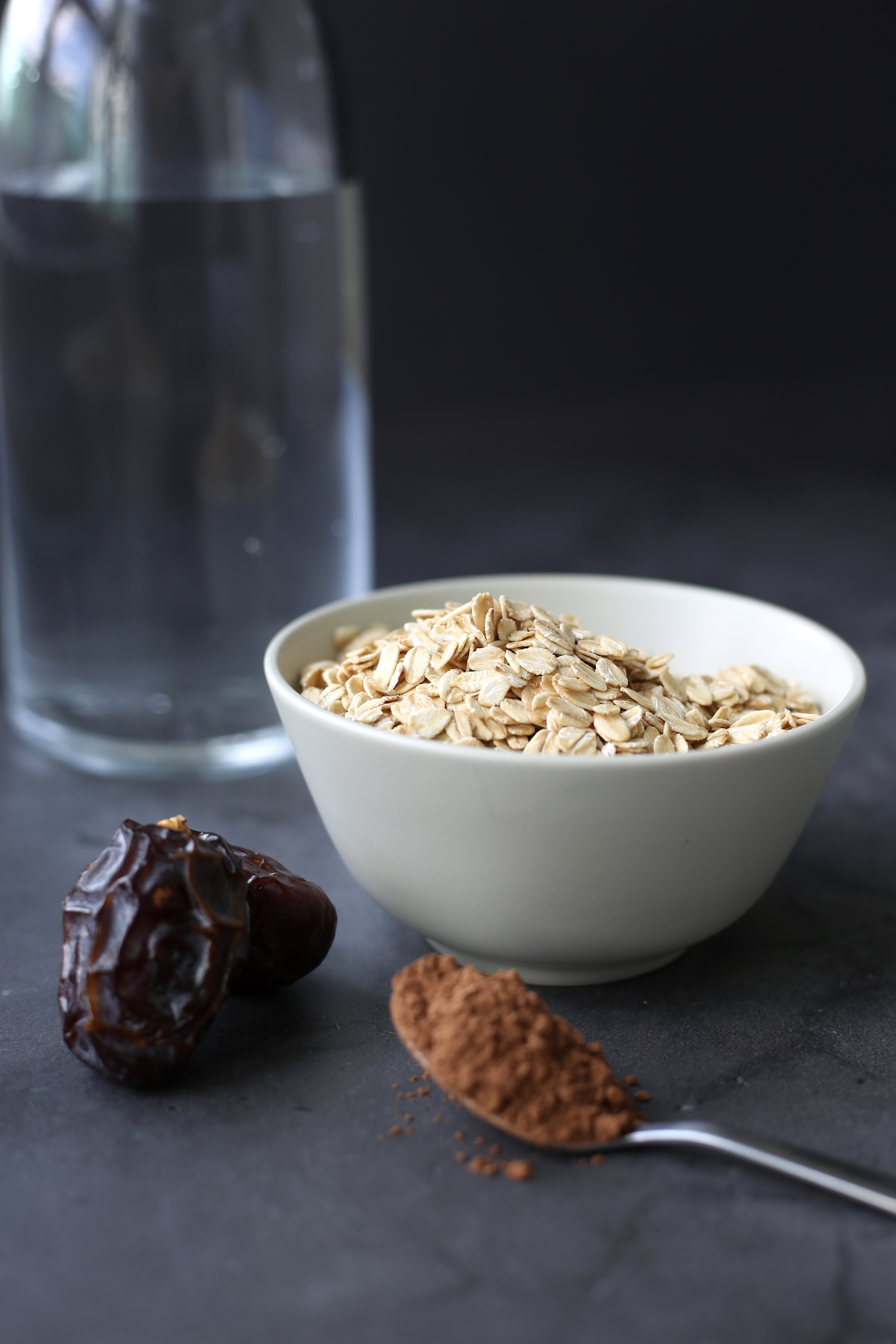 the ingredients for homemade chocolate oat milk layed out on a table