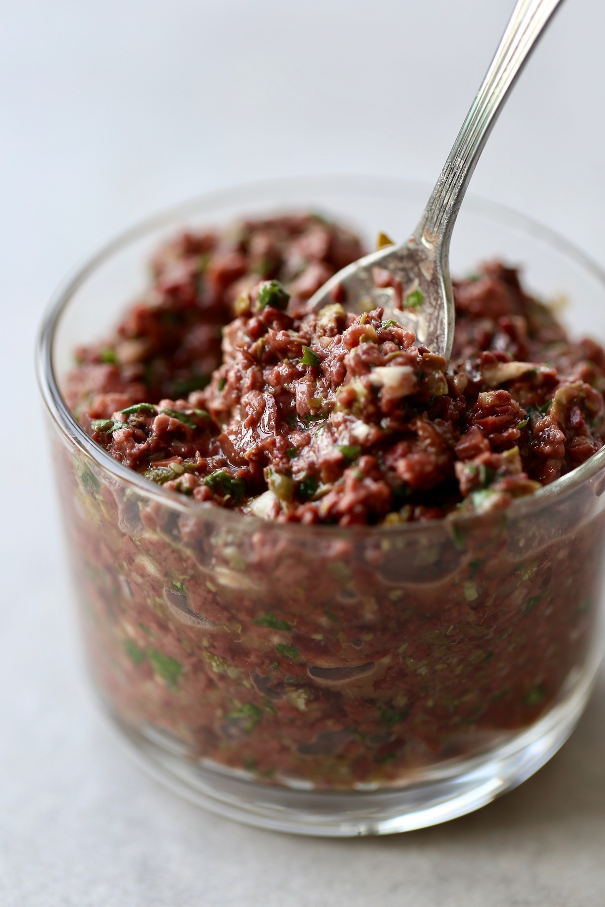 Homemade tapenade being scooped up with a spoon